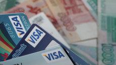 Пластиковые карты Visa и денежные купюры достоинством 1000 и 5000 рублей. Архивное фото