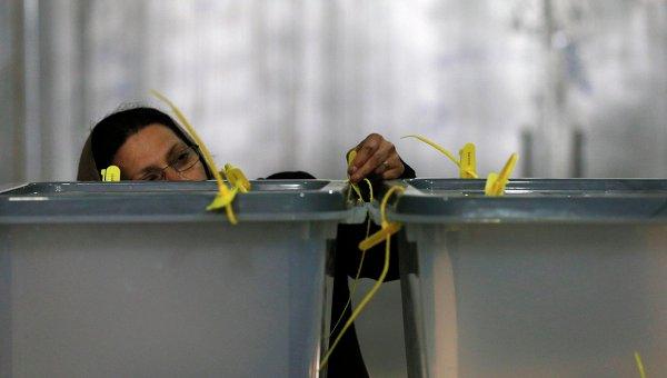 Работница проверяет замок на избирательной урне во время выборов президента в Афганистане