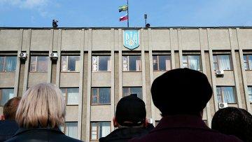 Сторонники федерализации Украины собрались перед зданием городской администрации Славянска, на крыше которого видны флаги России и Донецка
