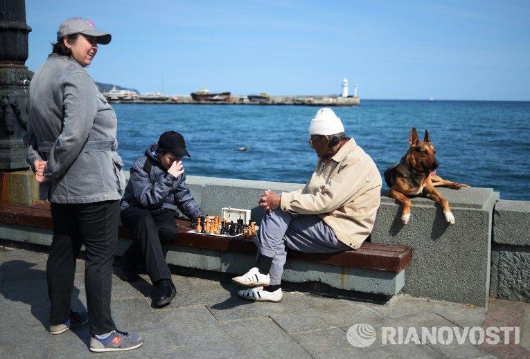 Отдыхающие играют в шахматы на набережной в Ялте