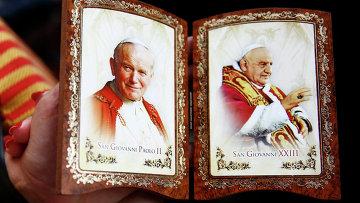 Католик держит сувенир с изображением папы Иоанна Павла II во время церемонии канонизации в Ватикане