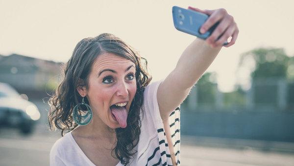 Девушка фотографируется на телефон