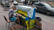 Мужчина играет на фортепиано на улице Крещатик в Киеве