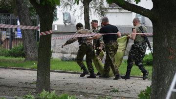 Народные ополченцы несут раненого в результате авианалета ВВС Украины на здание обладминистрации в Луганске