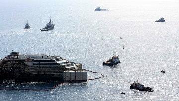 Круизный лайнер Коста Конкордия в окружении буксиров во время перемещения в порт Генуи