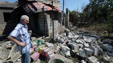 Житель Луганска у дома, разрушенного во время артиллерийского обстрела украинской армией