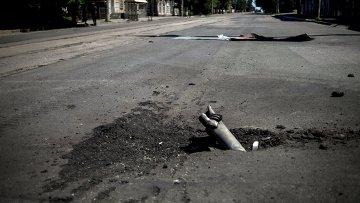 Фрагмент снаряда застрявший в асфальте после артиллерийского обстрела. Архивное фото
