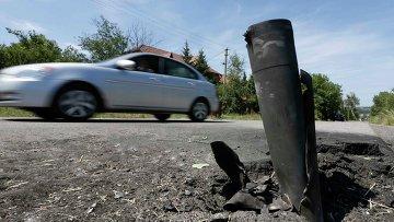 Машина на разбитой снарядами дороге в Донецкой области