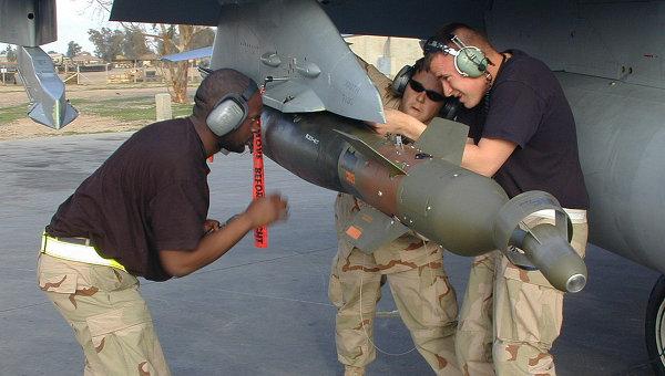 Американские военные закрепляют бомбу на крыле истребителя F-16