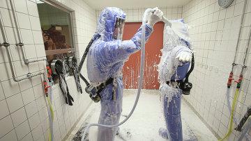 Медсестра и врач тропической медицины, одетые в изоляционные костюмы проходят процедуру дезактивации