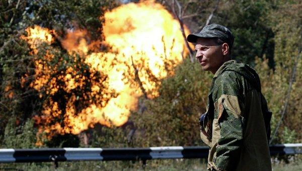 Боец народного ополчения возле газопровода, который загорелся в результате обстрела Донецка 15 августа 2014