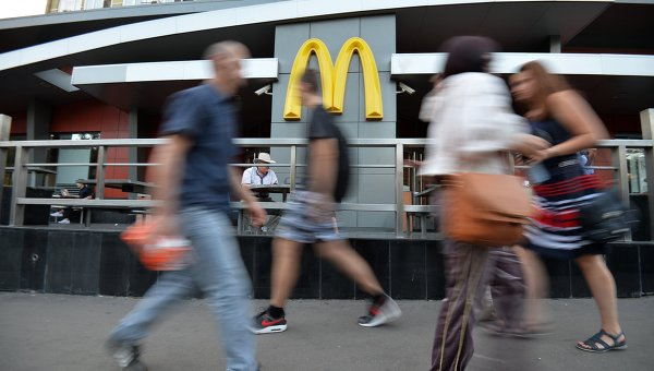 Люди проходят мимо ресторана быстрого питания Макдоналдс. Архивное фото
