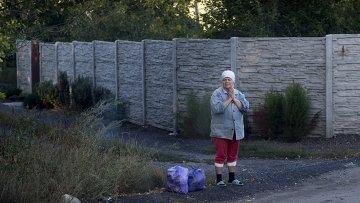 Женщина стоит у дороги под Донецком. Архивное фото