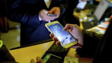 Посетитель московского магазина знакомится с функциями смартфонов Apple. Архивное фото