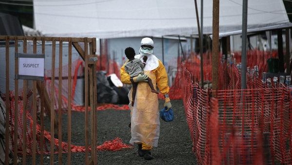Доктор из организации Врачи без границ несет на руках ребенка с подозрением на вирус Эбола, Либерия. 9 октября 2014
