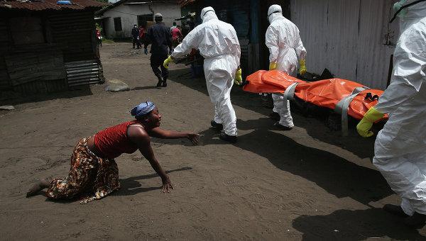 Члены команды захоронения несут тело женщины, умершей от Эболы. Архивное фото