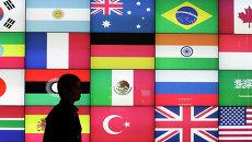 Мужчина проходит мимо экрана с флагами стран G20.  Архивное фото