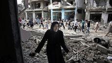 Палестинская женщина у разрушенного ударами Израильской армии дома