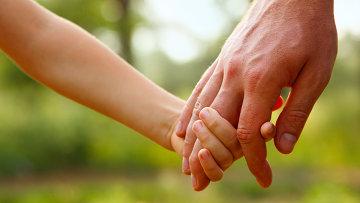 Ребенок держит за руку взрослого. Архивное фото