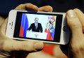 Житель Новосибирска смотрит на экране смартфона телевизионную трансляцию послания президента РФ Владимира Путина к Федеральному Собранию