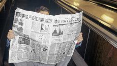 Пассажир московского метро читает газету Московский комсомолец