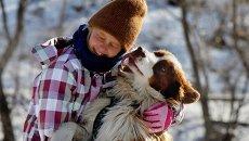 Девочка играет с австралийскими овчарками во время предновогодних соревнований Веселые старты ездовых собак