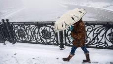 Прохожая на Патриаршем мосту в Москве во время снегопада