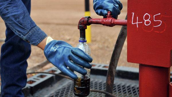 Инженер берет образец нефти на одной из скважин. Архивное фото