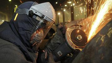 Рабочий во время обработки изделий на сталелитейном производстве. Архивное фото