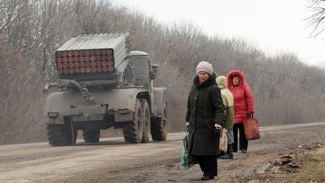 Жители Дебальцево на обочине дороги, по которой следует военная техника
