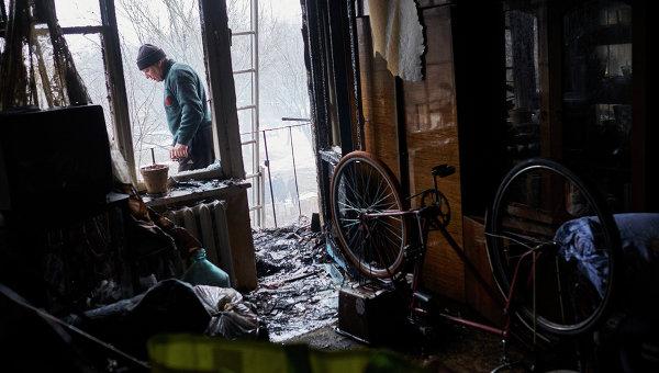 Мужчина в квартире, поврежденной в результате обстрела химического завода и жилого квартала в Донецке