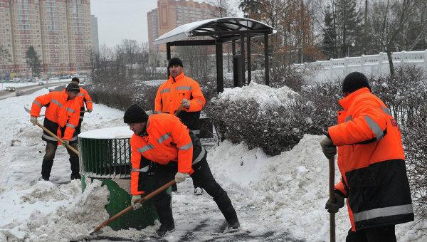 Сотрудники коммунальных служб убирают снег с территории автобусной остановки. Архивное фото