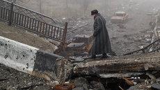 Пожилая женщина идет по разрушенному мосту возле аэропорта Донецка, Украина