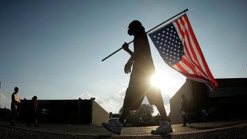 Человек с перевернутым американским флагом в городе Фергюсон, США