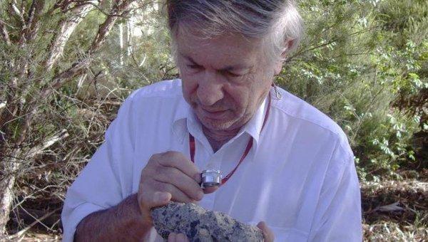 Профессор Гликсон изучает образец породы, сжатой и переплавленной в ходе падения астероида