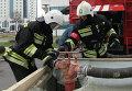Сотрудники МЧС РФ подключают пожарный рукав к гидранту во время учений