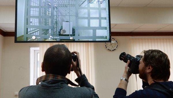 Корреспонденты фотографируют изображение одного из подозреваемых в убийстве политика Бориса Немцова Хамзата Бахаева. Архивное фото
