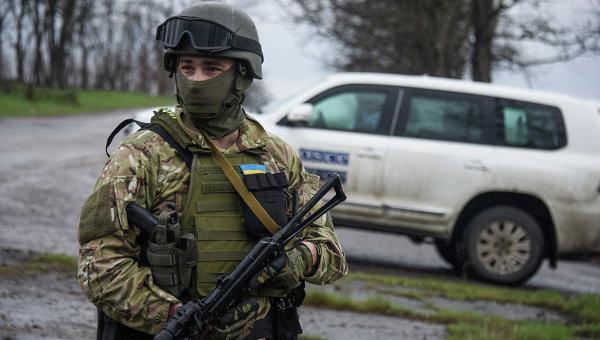 Украинский военный возле машины наблюдателей ОБСЕ