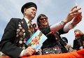 Девушка делает селфи с ветераном во время празднования 70-летия Победы в Великой Отечественной войне 1941-1945 годов в городе Казань