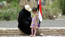 Женщина и ребенок с флагом Йемена. Архивное фото