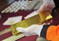 Золотой слиток в руках рабочего в цехе по выпуску заготовок и готовой продукции на Екатеринбургском заводе по обработке цветных металлов