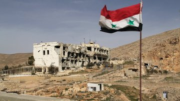Сирийский флаг на фоне разрушенного дома в сирийском городе Маалюля в 55 км от Дамаска. Архивное фото