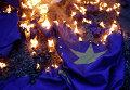 Демонстранцы жгут флаг на акции протеста против принятия проекта соглашения ЕС в Афинах