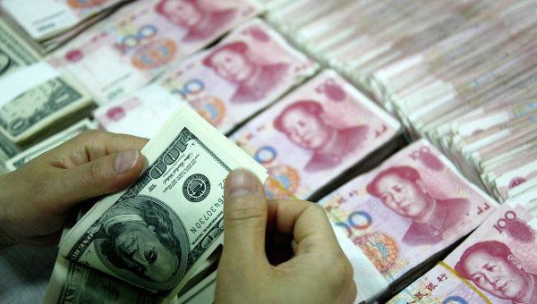Банковский служащий пересчитывает доллары рядом с пачками юаней. Архивное фото