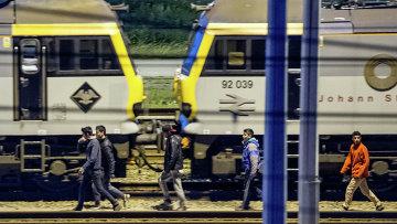 Мигранты идут вдоль железнодорожных путей в терминале Евротуннеля. Архивное фото