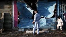 Афганец стоит рядом с поврежденным в результате взрыва магазином в Кабуле