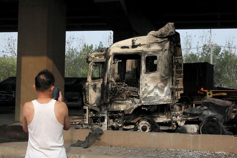 Поврежденный автомобиль в результате взрывов на складе опасных веществ в промышленном городе Тяньцзинь в Китае