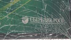 Рабочие собирали осколки выбитых взрывом стекол отделения Сбербанка РФ в Киеве