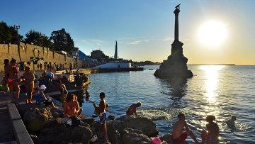 Отдыхающие и местные жители купаются у памятника затопленным кораблям на закате недалеко от Приморского бульвара в Севастополе. Архивное фото