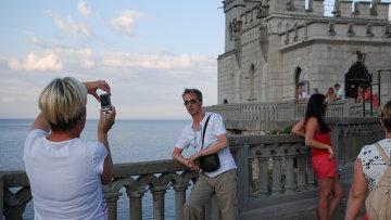 Туристы фотографируются на фоне Ласточкиного гнезда в Крыму. Архивное фото